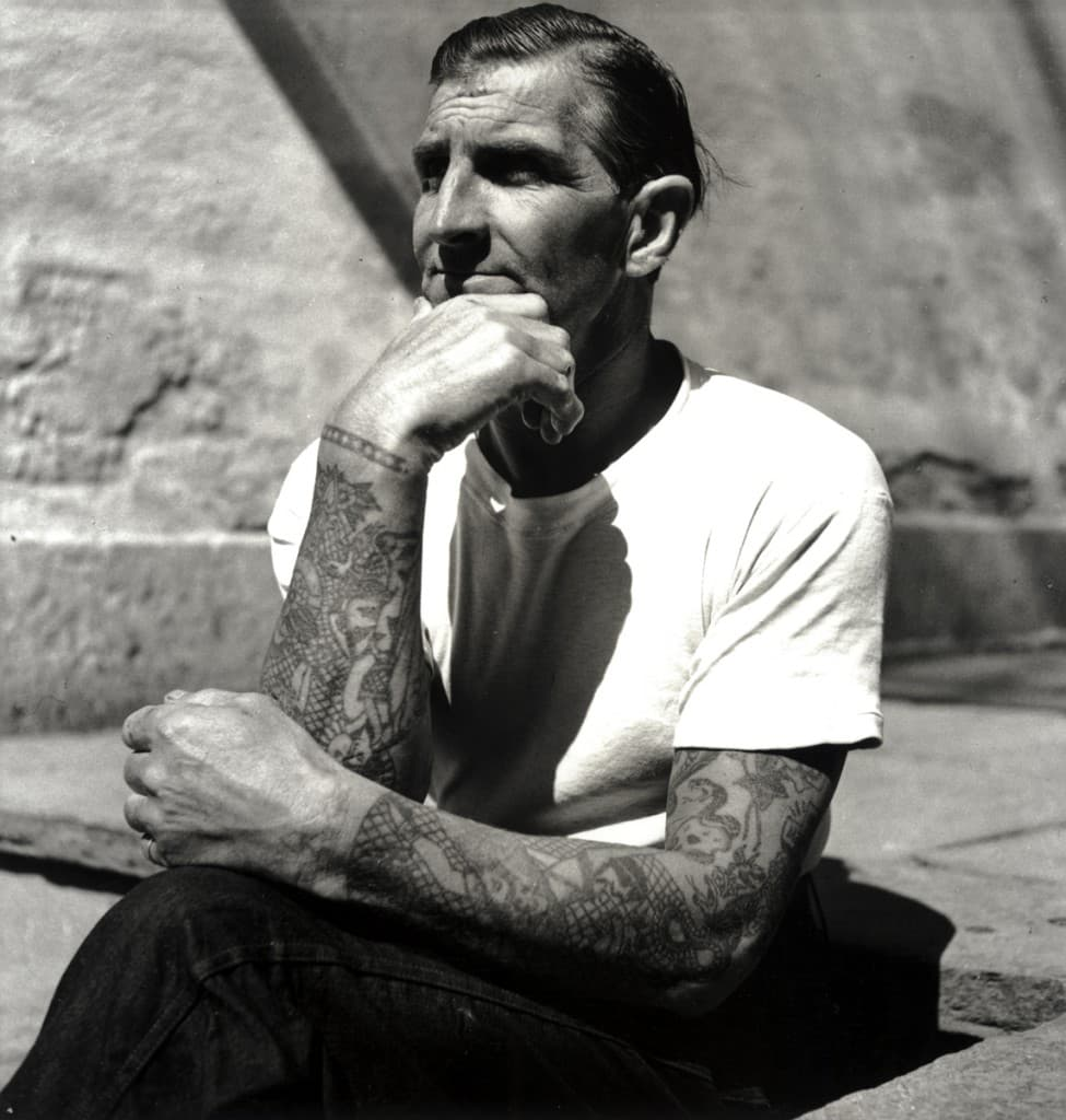 man with tattoos pondering