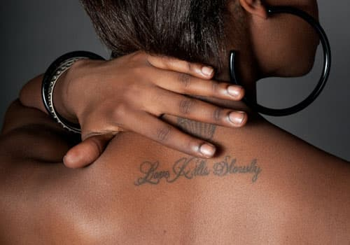 hand covering tattoo on neck of black woman