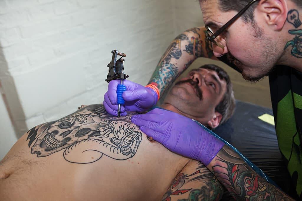 tattoo artist inking client