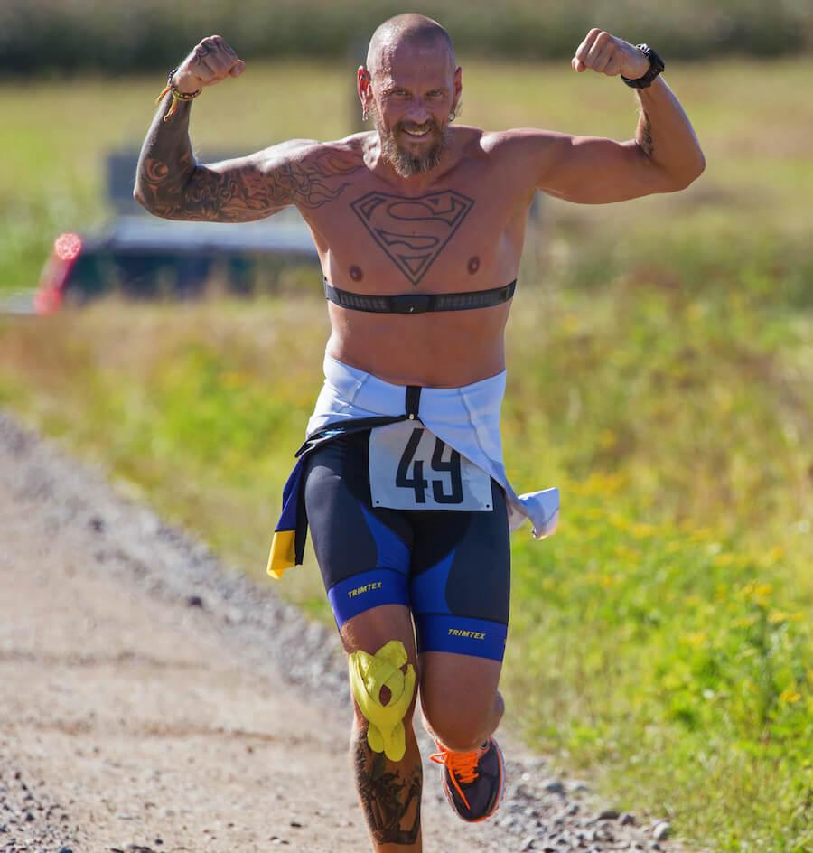man with tattoo superman running